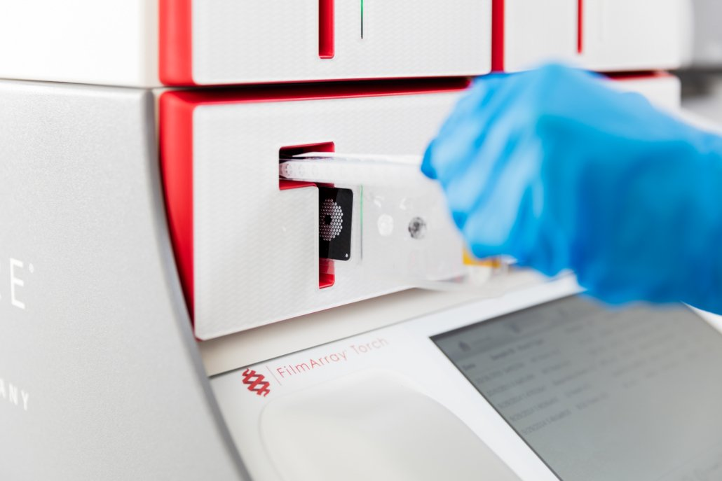 Person loading a syndromic testing pouch into a BioFire® System.